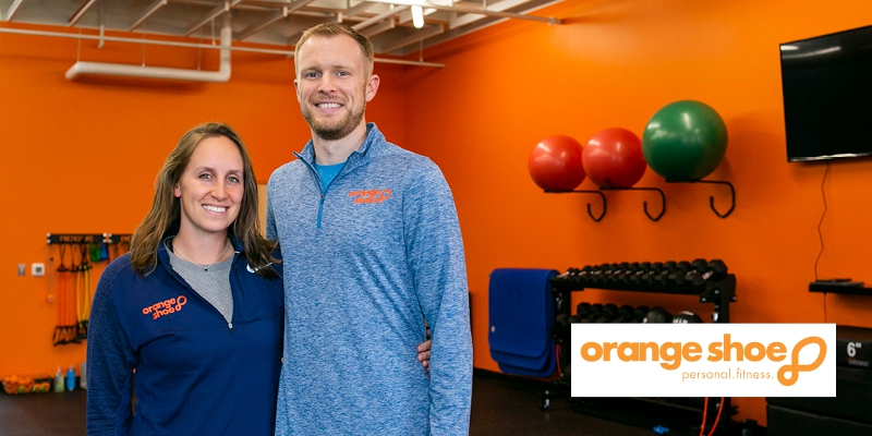 Emily and John McKiddy of Orange Shoe Personal Fitness smiling inside gym with orange walls with workout equipment behind them